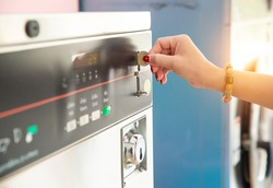 Female hand ready to insert a token into the slot of vintage chrome coin on the washing machine. Asian woman hand putting coin in washer machine for operated, inside laundrette, closeup