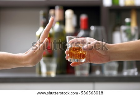 Female hand rejecting glass with alcoholic beverage on blurred background #536563018