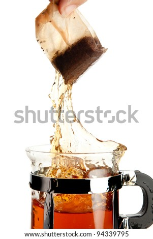 Female hand removing a tea bag with a splash