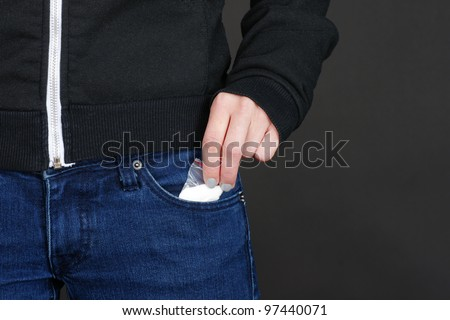 Female hand retrieving drug packet our of her blue jean pocket with copy space on black.