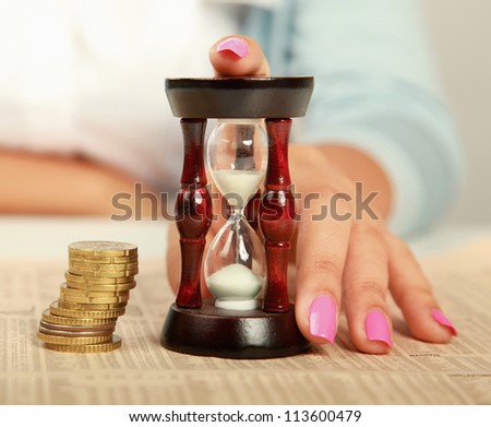 Female hand's with hourglass and coin