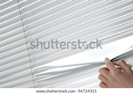 Female hand separating slats of venetian blinds with a finger to see through.