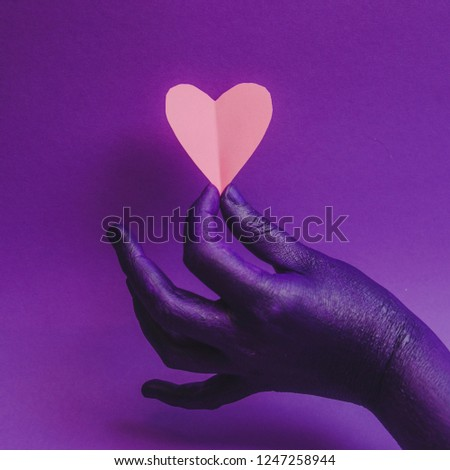 Female hand, showing beauty and skin care symbolism. Holding paper craft pink heart. fashion background, purple neon colors. Minimalism 