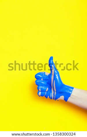 """female hand showing sign thumb up with paint flowing down on a colored background. creative idea, creative concept, gesture """"class"""" #1358300324"""