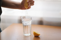 Female hand squeeze lemon juice in glass with water. Water with lemon. Fresh drink on quarantine