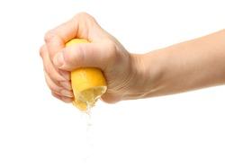 Female hand squeezing half of lemon on white background