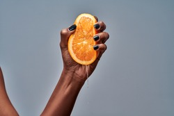 Female hand squeezing orange isolated on grey. Copy space