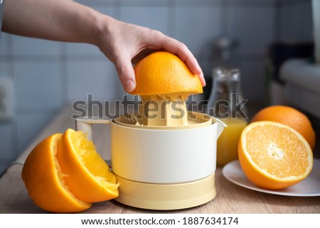 Female hand squeezing orange juice from fresh oranges with a juicer in the home kitchen, ?lose up. Stockfoto ©