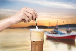 Female hand stirring a straw on a greek cold coffee, freddo cappuccino at a beach.