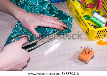 Female hand tailor a dress of green tissue #568870318