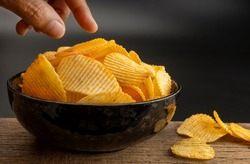Female hand take potato chips from bowl on black background