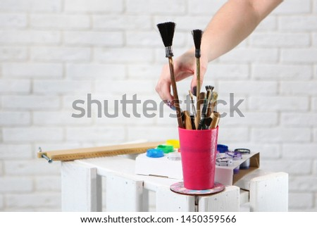 Female hand takes a brush for drawing. Brushes for painting are in the cup. Photo on the background of a white wall with a brickwork effect. Concept hobbies and hobbies. Photos in the interior.