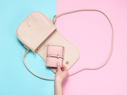 Female hand takes leather wallet from bag on pastel background. Top view, flat lay, minimalism