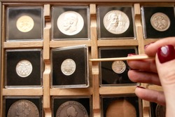 Female hand taking out a metal coin in a transparent plastic protection square capsule from a wooden display case with numismatic collection with a wooden stick. Coin holder case for numismatist.
