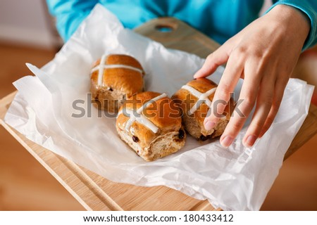 Female hand taking traditional Easter cross-bun and other hand holding cross buns served on white baking paper placed on chopping board