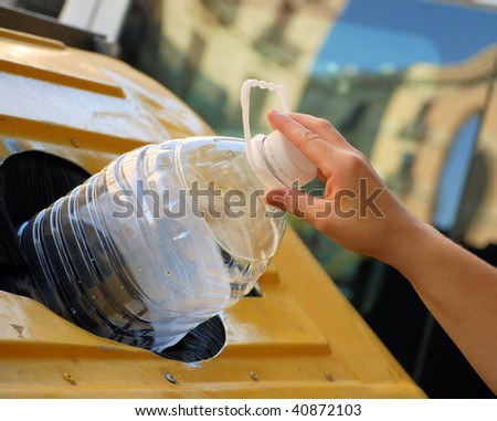female hand throwing out a plastic large bottle in container for processing and recycling