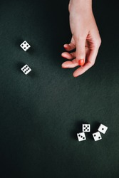 Female hand tossing dices. White square dices against a black background.