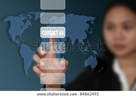 female hand touch on contact us button with world map background