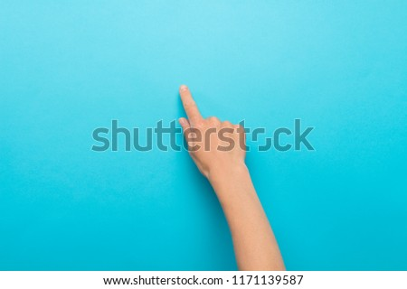 Female hand touches finger a blue background. Flat lay, top view #1171139587