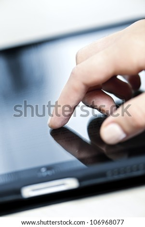 Female hand touching tablet computer screen with finger