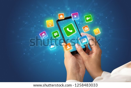 Female hand using smartphone with 3D shiny starlike application icons around #1258483033