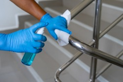 Female hand using wet wipe and alcohol sanitizer spray to clean stainless steel staircase railing.Antiseptic,disinfection ,cleanliness and heathcare, Anti Corona virus (COVID-19). Selective focus.