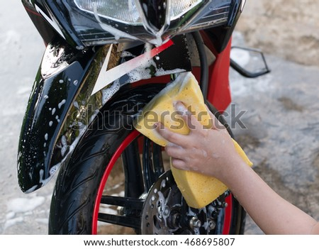 Female hand washing a motorcycle. #468695807