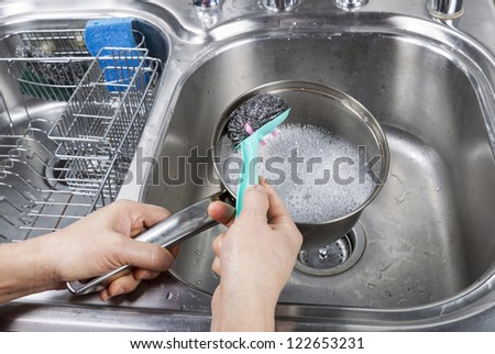 Female hand washing stainless steel pan with steel pad brush and soapy water in kitchen sink