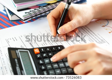 Female  hand  with a calculator and a pen, business  graphics, and  Diagram.