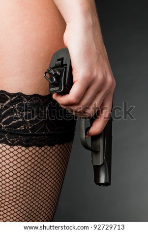 Female hand with a gun on a dark background in stockings