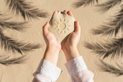 Female hand with a handful of sand with sun hand-drawn among shadow of a palm tree branch of a sandy tropical beach. Holiday concept. Creative, background, travel, summer. Flat lay