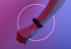 Female hand with a smart bracelet. Modern gadgets. Creative pop art pink blue neon color. Trendy gradient illumination. Night light
