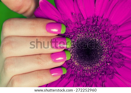 Female hand with bi color manicure on the flower