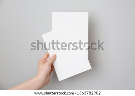 Female hand with blank invitation cards on light background #1363782902