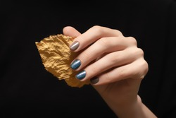 Female hand with blue gray nail design. Glitter blue nail polish manicure. Female hand hold autumn leaf