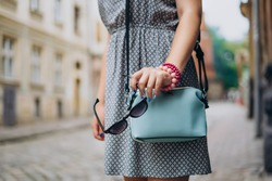 Female hand with blue handbag. Female hand with manicure and bracelets holding sunglasses. Stylish woman in dress with accessories