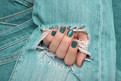 Female hand with blue nail design. Blue nail polish manicure. Woman hand on blue ragged denim fabric background