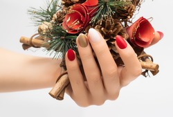 Female hand with Christmas nail design. Red and gold nail polish manicure. Female hand hold New Year decoration