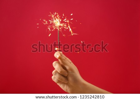 Female hand with Christmas sparkler on color background #1235242810