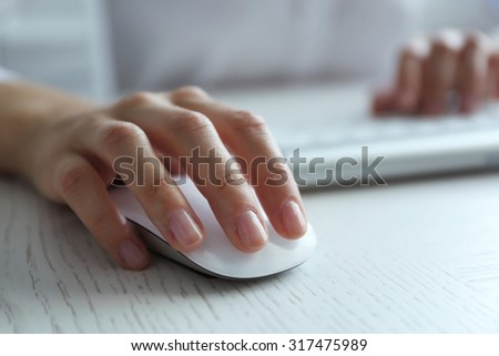 Female hand with computer mouse on table, closeup #317475989