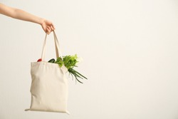Female hand with eco bag on white background. Zero waste concept