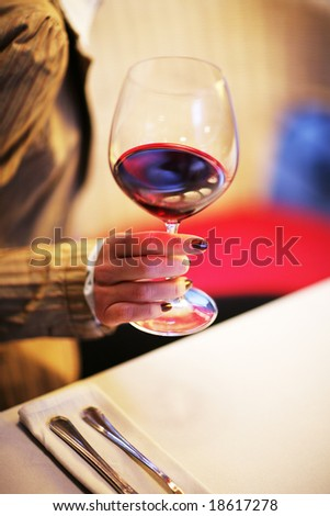 Female hand with glass of red wine. Shallow DOF.