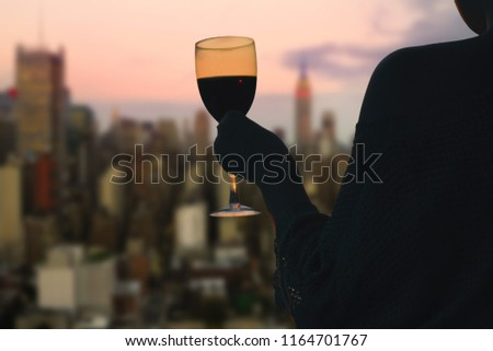 Female hand with glass of wine on Manhattan background. New York city.  Service on the roof of the restaurant