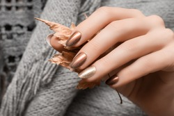 Female hand with gold nail design. Brown nail polish manicured hand. Woman hand hold yellow autumn leaf
