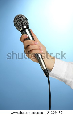 female hand with microphone, on blue background
