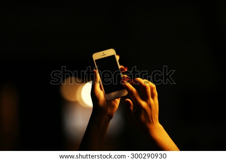 Female hand with mobile phone on blurred night lights background