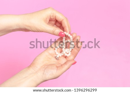 female hand with pearls on pink #1396296299