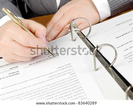 Female hand with pen signing a contract.