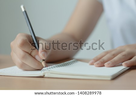 Female hand with pen writing on notebook.Woman  Wearing white T-shirt.