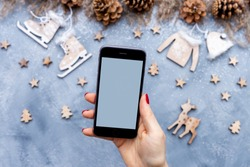 Female hand with red nail polish holding a blank smart mobile phone above grey table with Christmas wooden decoration and pine cones